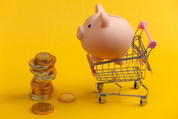 Tema di acquisto. mini carrello per supermercati con salvadanaio e monete su giallo.