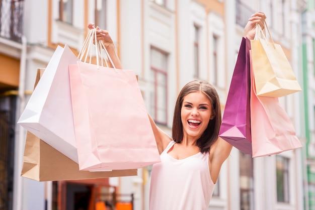 La shopping therapy la rende felice. attraente giovane donna che tiene le borse della spesa e sorride mentre sta in piedi all'aperto
