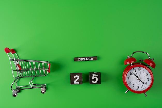 Concetto di tempo di acquisto. carrello del supermercato con sveglia e data di festeggiare il 25 dicembre