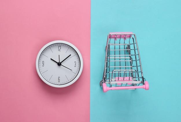 Tempo per lo shopping. carrello del supermercato con l'orologio su sfondo blu rosa. minimalismo. vista dall'alto