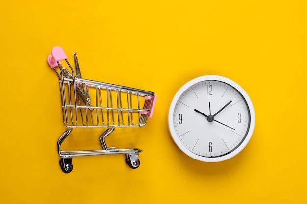 Tempo per lo shopping. carrello del supermercato con l'orologio su uno sfondo giallo. minimalismo. vista dall'alto