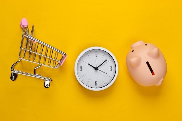 Tempo per lo shopping. carrello per supermercato con salvadanaio, orologio su uno sfondo giallo. minimalismo. vista dall'alto