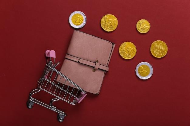 Tempo di acquisti. carrello del supermercato con portafoglio, monete su un rosso
