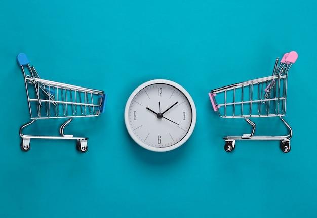 Tempo per lo shopping. carrelli per supermercati con orologio su sfondo blu. minimalismo. vista dall'alto
