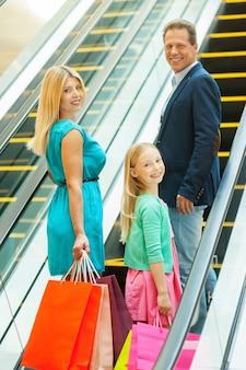 Fare la spesa insieme è divertente! famiglia allegra che tiene le borse della spesa e si guarda alle spalle mentre sale con la scala mobile