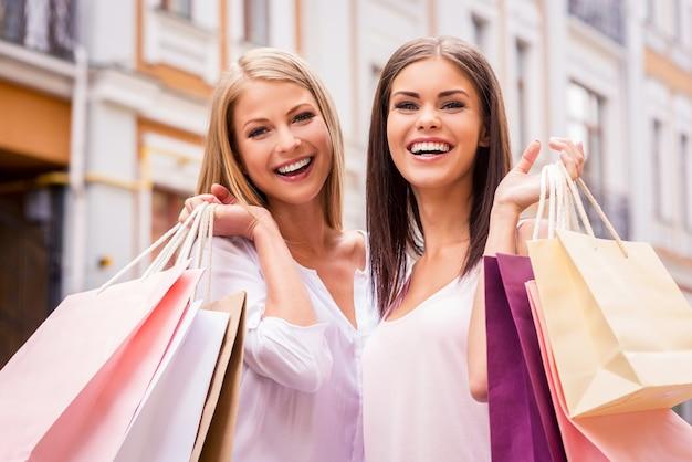 Fare la spesa insieme è divertente. due giovani donne attraenti che tengono le borse della spesa e sorridono mentre stanno in piedi all'aperto