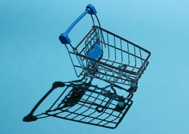 Carrello della spesa su uno sfondo blu con le ombre. mini concetto di acquisto