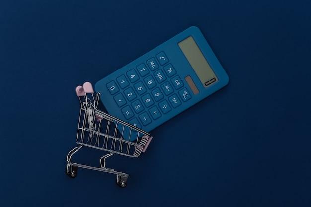 Carrello della spesa e calcolatrice su sfondo blu classico. costi del supermercato. colore 2020. vista dall'alto.