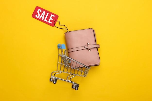 Carrello della spesa e portafoglio in pelle alla moda con etichetta di vendita rossa su giallo.