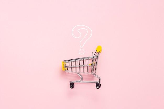 Carrello della spesa dal supermercato su uno sfondo rosa isolato. shopping nel centro commerciale, negozio, shopping, una vasta scelta. punto interrogativo. vista piana, vista dall'alto.