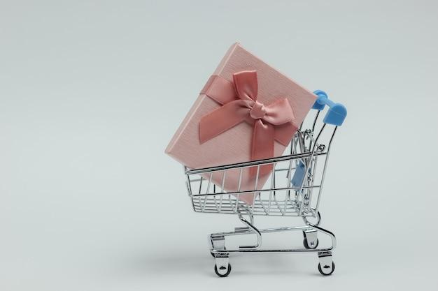 Carrello della spesa e confezione regalo con fiocco su sfondo bianco. composizione per natale, compleanno o matrimonio.