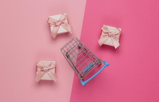 Carrello della spesa e scatole regalo con fiocchi su sfondo rosa pastello. composizione per natale, compleanno o matrimonio. vista dall'alto