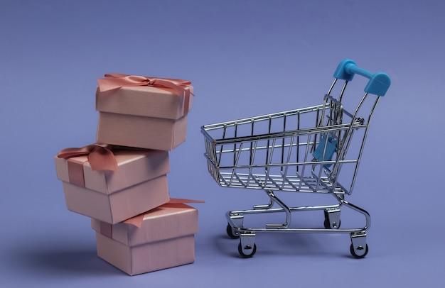 Carrello della spesa e scatole regalo con fiocchi su sfondo viola. composizione per natale, compleanno o matrimonio.