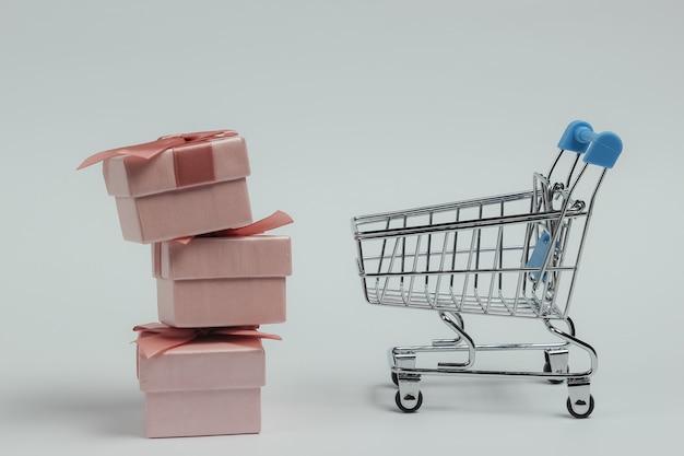Carrello della spesa e scatole regalo con fiocchi su sfondo bianco. composizione per natale, compleanno o matrimonio.
