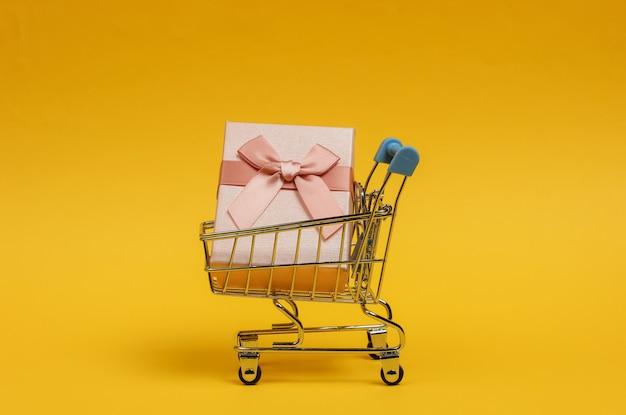 Carrello della spesa e scatole regalo con fiocchi su sfondo giallo. composizione per natale, compleanno o matrimonio.