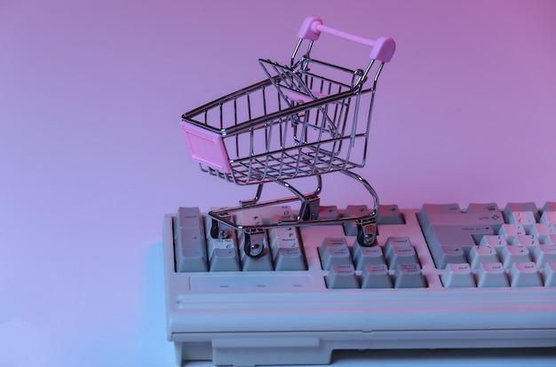 Carrello della spesa sulla vecchia tastiera del pc. neon sfumato blu rosa, luce olografica. shopping online retrò