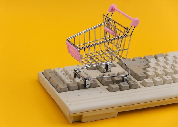 Carrello della spesa sulla vecchia tastiera del pc. sfondo giallo. shopping online retrò