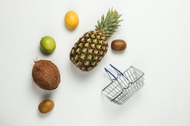 Carrello della spesa e frutti tropicali su sfondo bianco. fare la spesa al supermercato. concetto di cibo sano. vista dall'alto. copia spazio