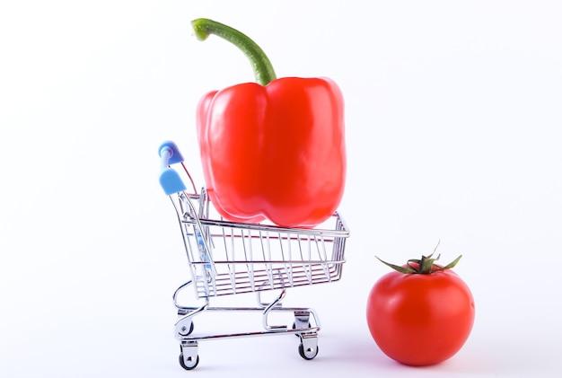 Carrello della spesa con peperone e pomodoro su un bianco