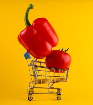Carrello della spesa con peperone e pomodoro su giallo