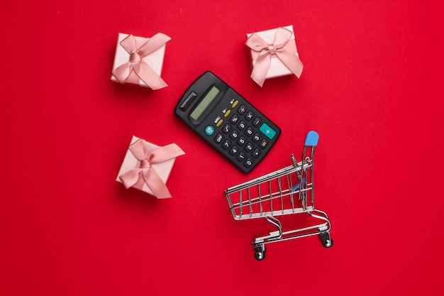 Carrello della spesa con calcolatrice, scatole regalo sul rosso.