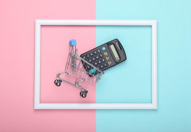 Carrello della spesa con la calcolatrice in una cornice bianca sulla superficie pastello blu rosa