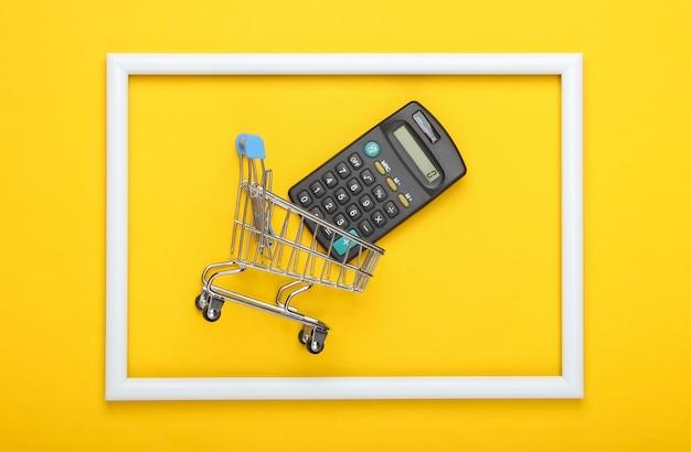 Carrello della spesa con la calcolatrice in una cornice bianca su superficie gialla