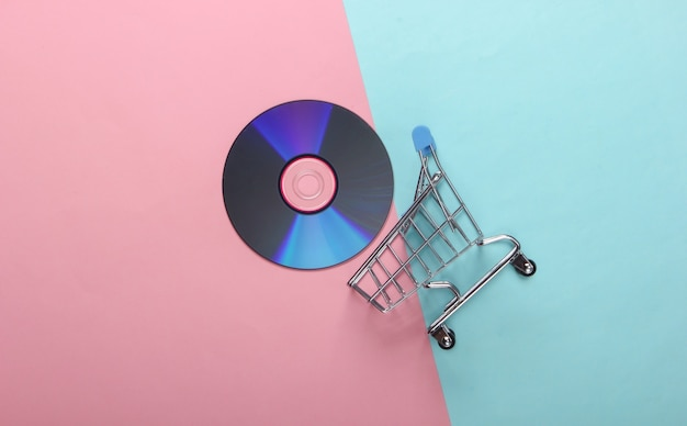Carrello della spesa con disco cd su superficie pastello blu-rosa