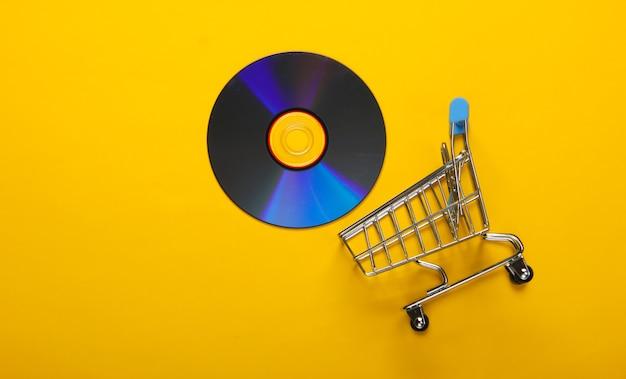 Carrello della spesa con disco cd su superficie gialla