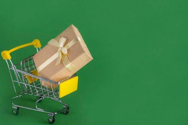 Carrello della spesa con scatola natalizia. spazio del testo