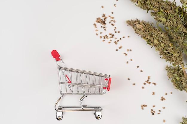 Carrello della spesa con foglia di cannabis secca e ramoscelli su sfondo bianco vista dall'alto con semi di canapa
