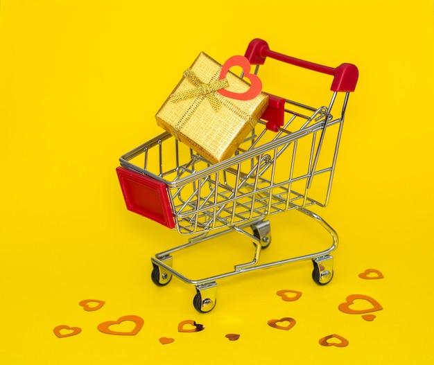 Carrello della spesa con regalo d'oro e coriandoli rossi su sfondo giallo.