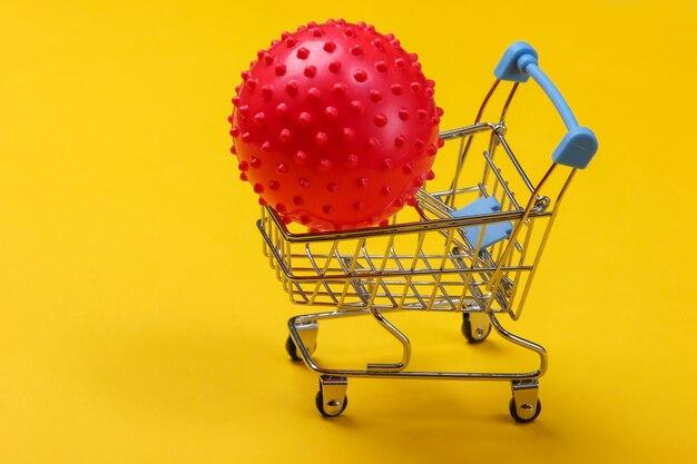 Carrello della spesa con sfera di massaggio su colore giallo