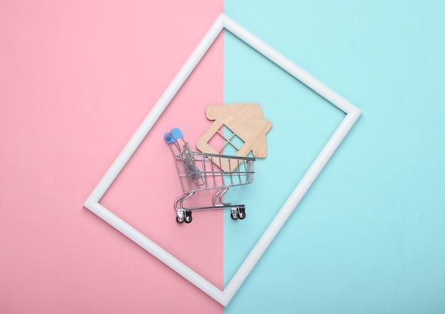 Carrello della spesa con mini casa in una cornice bianca su superficie pastello blu rosa