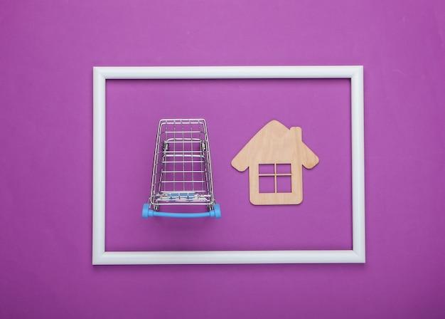 Carrello della spesa con mini casa in una cornice bianca su superficie viola