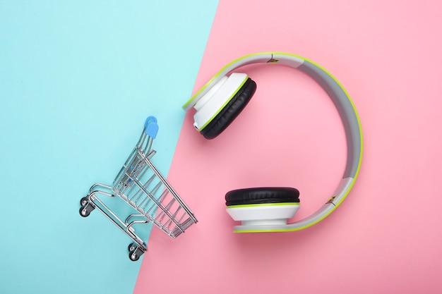 Carrello della spesa con nuove cuffie stereo sulla superficie rosa blu