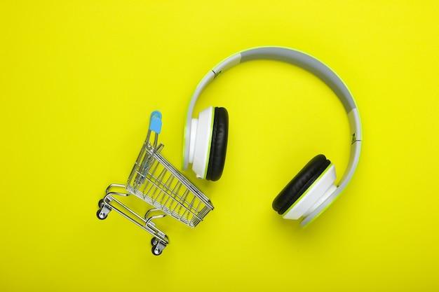 Carrello della spesa con nuove cuffie stereo su una superficie verde