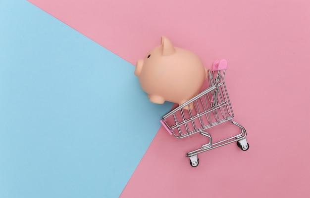 Carrello della spesa con salvadanaio su sfondo blu-rosa pastello. vista dall'alto
