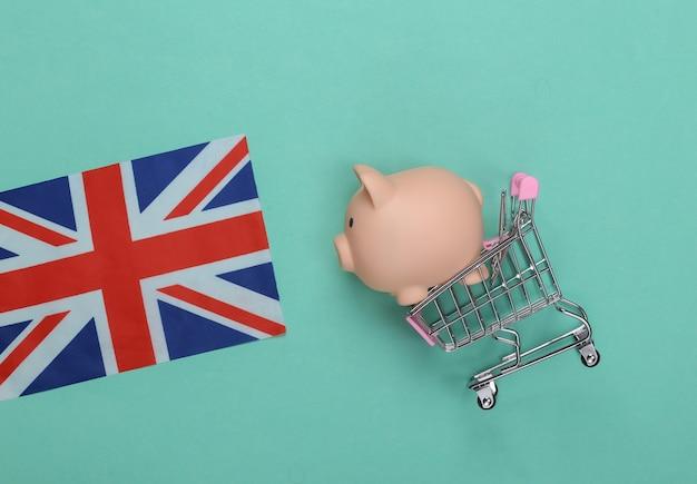 Carrello della spesa con salvadanaio e bandiera britannica su verde menta.