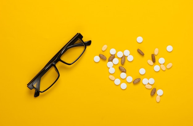 Carrello della spesa con le pillole su colore giallo