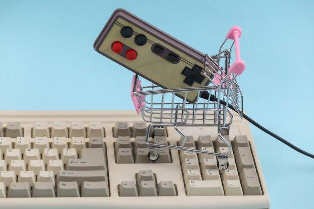 Carrello della spesa con gamepad retrò sulla vecchia tastiera del pc. sfondo blu. attributi retrò anni '80