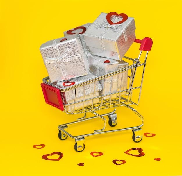 Carrello della spesa con regalo d'argento e coriandoli rossi su sfondo giallo.