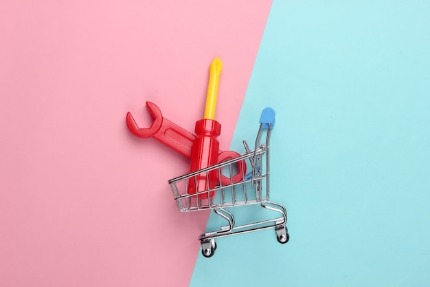 Carrello della spesa con strumento da lavoro giocattolo su un pastello blu-rosa.