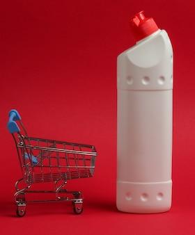 Carrello della spesa con bottiglia di plastica bianca di detersivo per il bagno e la toilette su uno sfondo rosso.