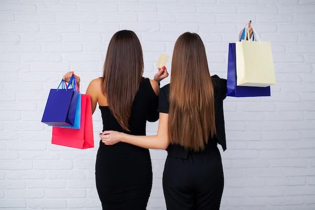 Shopping. due donne che tengono borse colorate su sfondo chiaro durante le vacanze del venerdì nero.