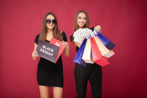 Shopping. due donne che tengono borse colorate su sfondo rosso in vacanza venerdì nero.