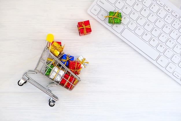 Acquisti nel webstore. carrello, scatole regalo e vista dall'alto della tastiera. concetto di acquisto online di natale
