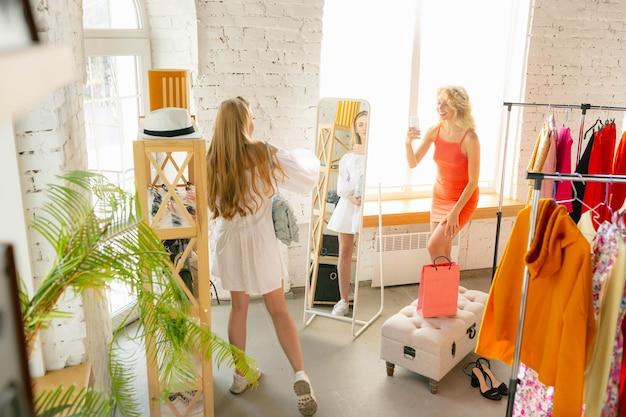 Shopping con gli amici indossa il negozio di abbigliamento durante i saldi della collezione estiva o autunnale