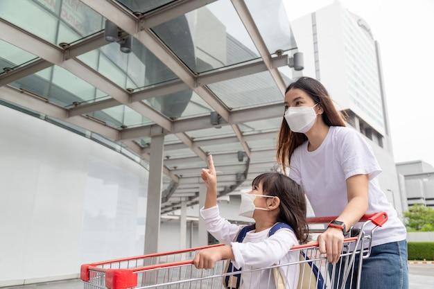 Fare shopping con i bambini durante un'epidemia di virus. asian madre e figlia che indossano una maschera chirurgica per andare al supermercato.