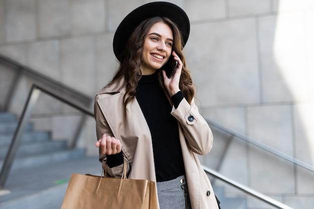 Giovane donna di acquisto che parla sul telefono e che tiene i sacchetti nel centro del centro commerciale